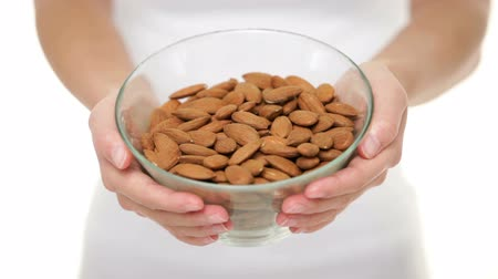 mandula : Almonds nuts - woman showing raw almond bowl closeup. Healthy food concept in studio with hands lifting bowl of unprocessed almonds up to focus on white background.