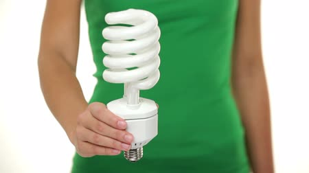 флуоресцентный : Energy saver light bulb - woman showing big fluorescent light bulb to camera. Green energy, bright idea concept on white background.