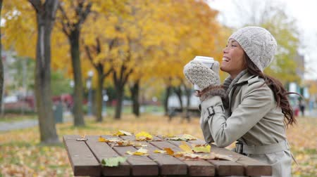 outside : Fall woman sitting in autumn park drinking coffee with colorful yellow leaves falling from trees. Smiling happy mixed race Asian Caucasian young female professional joyful outside. Stock Footage