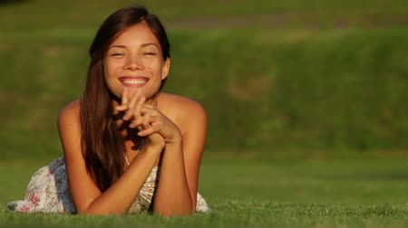 çim : Young beautiful woman smiling lying in grass in summer dress outside at sunset waving hello looking at camera. Happy joyful mixed race girl of Asian Caucasian ethnicity. Stok Video