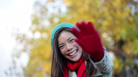 olá : Fall woman waving hello and blowing a kiss in beautiful autumn foliage forest. Happy smiling mixed race asian caucasian girl saying hi looking at camera outdoors. Stock Footage