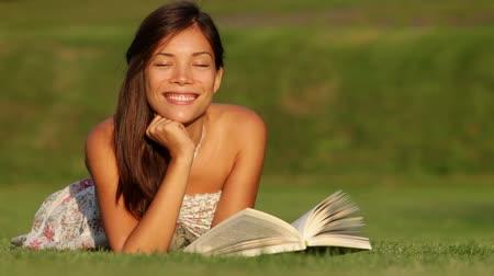 yeşil çimen : Girl reading book in park smiling happy, looking at book and looking joyful and cheerful at camera. Beautiful young mixed race Asian Caucasian woman enjoying lying in grass in summer dress.