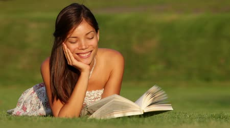 lefekvés : Girl reading book in park smiling happy looking at book joyful and cheerful. Beautiful young mixed race Asian Caucasian girl lying in grass in summer dress at sunset.