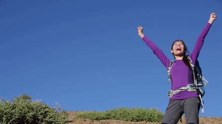 bajnok : Happy success winner hiker cheering after reaching a summit peak during hiking trek outdoors on Teide, Tenerife.Canary Islands, Spain. Happy celebrating multiracial Asian female on hike travel.
