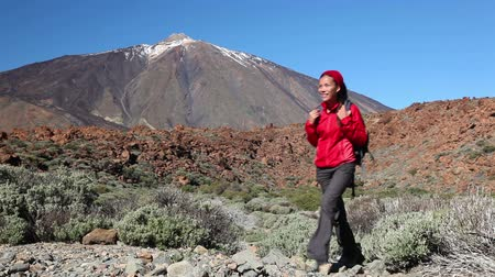 utazó : Active hiker woman hiking on Teide, Tenerife. Female trekking trough landscape scene smiling happy wearing backpack. Beautiful mixed race Asian Caucasian young woman on Tenerife, Canary Islands, Spain Stock mozgókép