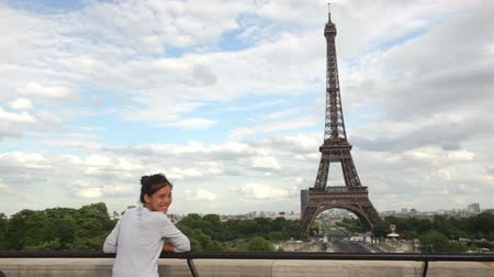 башни : Eiffel Tower Paris woman tourist enjoying view and waving looking away and waving at camera during travel tourism sightseeing in Paris, France, Europe. Beautiful young Asian Caucasian traveler