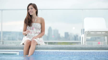 estilo de vida : Woman in city sitting at pool with skyline in background. Cute girl in summer dress relaxing enjoying luxury city lifestyle. Beautiful young multiracial Asian Caucasian model.