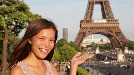 smíšené rasy osoba : Travel woman presenting showing Eiffel Tower in Paris. Happy tourist girl displaying Eiffel Tower with open palm hand gesture. Dostupné videozáznamy