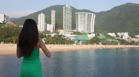 kaukázusi : Tourist woman taking picture photos with smart phone at Repulse Bay beach, Hong Kong. Beautiful Asian woman traveling in summer dress enjoying view. Hong Kong travel and tourism concept.