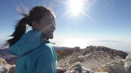 pohoří : Hiking woman on Teide volcano taking photo on top of the mountain smiling happy at camera. Candid girl in healthy lifestyle outdoor activity. Female hiker enjoying taking pictures. Dostupné videozáznamy