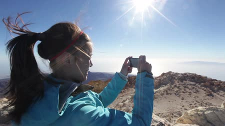 képek : Hiker woman photographing taking pictures on mountain summit top of the volcano, Teide, Tenerife of Canary Islands, Spain. Happy female hiking and taking photos. Mixed race Asian Caucasian girl hiker. Stock mozgókép