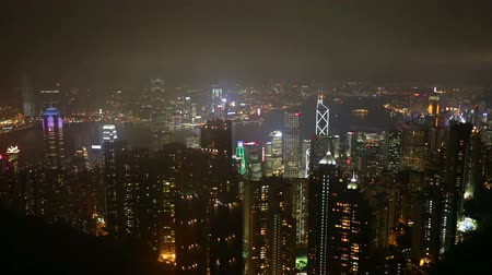 туристическим направлением : Hong Kong skyline at night from Victoria Peak. Timelapse footage showing city lights and downtown Hong Kong central and Victoria Harbour. Стоковые видеозаписи
