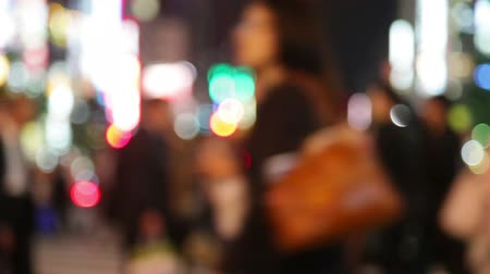 trabalho : Pedestrians - people walking in city night with lights. Out of focus background from busy big city with people crossing street. Tokyo, Japan.