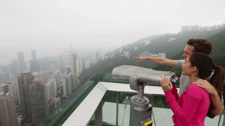 utazó : Hong Kong Victoria Peak tourists romantic couple enjoying view looking in binoculars over Hong Kong Island and Victoria Harbour. Young happy multiethnic couple traveling in Hong Kong. Travel concept.