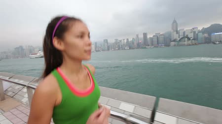 kimerül : Running woman runner jogging in Hong Kong city. Jogger training on Tsim Sha Tsui Promenade and Avenue of Stars in Victoria harbour, Kowloon, Hong Kong. Female fitness sport runner working out outdoor.