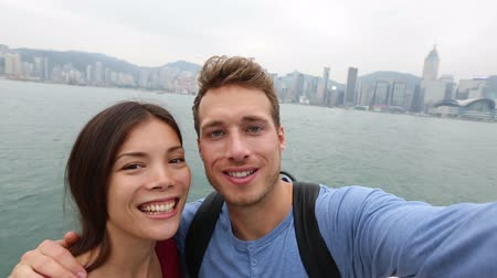 любовь : Tourists couple taking self portrait picture photo in Hong Kong enjoying view and sightseeing on Tsim Sha Tsui Promenade and Avenue of Stars in Victoria Harbour, Kowloon, Hong Kong. Travel concept.