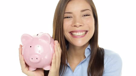svině : Piggy bank casual business woman showing piggybank in closeup on white background. Money and savings concept with multiracial female model saving money. Dostupné videozáznamy