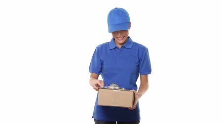 paket : Delivery courier - woman giving package wearing blue uniform. Woman courier smiling happy on white background. Beautiful young mixed race Caucasian  Chinese Asian female professional courier.