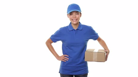 balík : Female package delivery courier person giving packages in blue uniform giving cardboard box. Woman courier smiling on white background. Beautiful young mixed race Caucasian  Chinese Asian female.