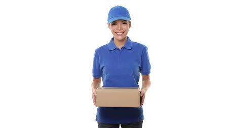 paket : Woman package delivery courier person giving packages wearing blue uniform giving cardboard box. Female courier smiling happy on white background. Beautiful young mixed race Caucasian  Chinese Asian. Stok Video