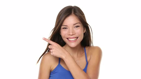 белый : Woman pointing showing happy on white. Beautiful girl pointing to both side with happy cheerful face expression on white background. Multiracial Chinese Asian  Caucasian female model in blue. Стоковые видеозаписи