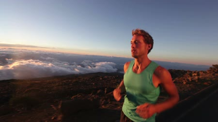 sportovní : Running man - jogging athlete runner training outdoor. Male jogger trail running exercising for marathon. Handsome fit Caucasian fitness model in his 20s at mountain above the clouds at sunset. Dostupné videozáznamy