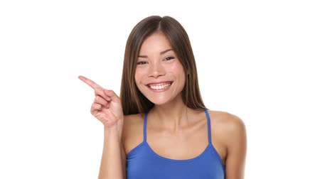 rosto humano : Woman pointing showing happy on white. Face close up beautiful girl pointing to both side after walking in and winking with happy cheerful face expression. Multiracial female model in blue. Vídeos