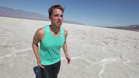 kimerül : Running man cross country runner in extreme desert. Male extreme ultra runner training and jogging as part of healthy fitness lifestyle. Fit athlete model in his 20s running in Death Valley, USA. Stock mozgókép