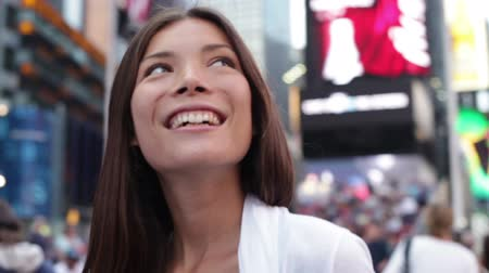 quadrado : Happy woman tourist in New York City, Manhattan, Times Square. Girl traveler looking around joyful and happy smiling at city lights in downtown New York. Multiethnic Asian Caucasian woman in her 20s. Vídeos