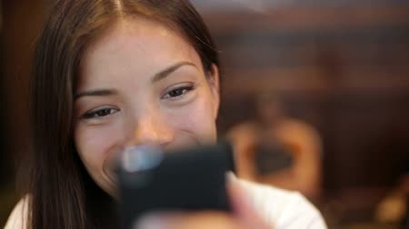 smile : Girl using smartphone in cafe drinking coffee laughing in cafe. Beautiful multicultural young female professional having casual conversation on mobile phone. Mixed race Asian Caucasian model. Stock Footage