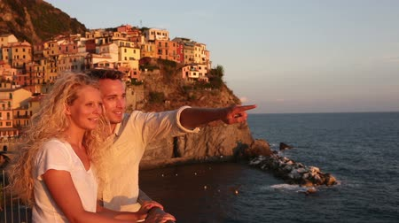 İtalyan : Couple in love by sunset on holidays travel. Romantic young beautiful couple enjoying ocean view romance. Young people, man and woman traveling on vacation in Manarola, Cinque Terre, Liguria, Italy
