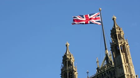 reino unido : British flag on Palace of Westminster, Houses of Parliament in London, United Kingdom. The UK flag, Union Jack against clear blue sky. Vídeos