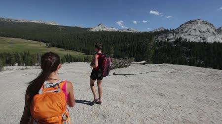 utazó : Hikers people hiking in Yosemite. Hiker couple walking on hike wearing backpacks. Happy sporty couple walking down from the Pothole Dome, Yosemite National Park, California, USA.