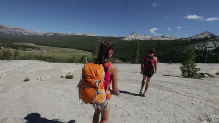 kamp : Hikers people hiking in Yosemite. Hiker couple walking on hike wearing backpacks. Happy sporty couple walking down from the Pothole Dome, Yosemite National Park, California, USA.