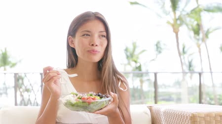 estilo de vida saudável : Healthy lifestyle woman eating salad smiling happy outdoors on beautiful day. Young female eating healthy food outside in summer dress laughing and relaxing in sofa. Pretty multiracial model.