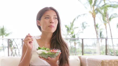 salad : Salad - healthy eating woman laughing eating food snack enjoying beautiful day sitting in sofa. Pretty mixed race Asian Caiucasian female model in white summer dress. Stock Footage