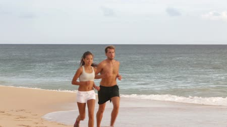 plaz : People running - young couple jogging on beach. Attractive fit sporty young couple runners side by side on the beach in the summer sunshine enjoying the fresh air as they train together Dostupné videozáznamy