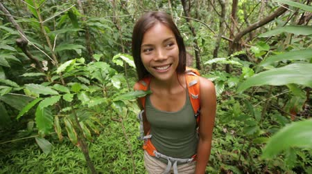 hawaii : Hiking - woman hiker walking in rain forest. Trekking young female on hike through dense rainforest nature on Maui, Hawaii, USA. Healthy young sporty multiracial Asian girl living active lifestyle.