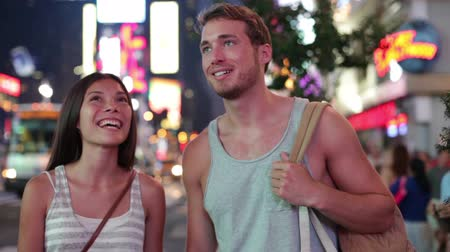 namoro : People in New York - happy couple on Times Square. Dating young couple in love walking and talking. Beautiful young multiracial tourists on fun date in city, Manhattan, USA. Asian woman, Caucasian man