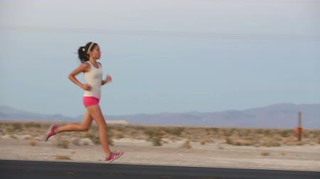 двадцатые годы : Running woman sprinting on highway road at sunset at countryside in USA. Fit female fitness girl training outdoor in beautiful landscape. Multiracial Caucasian Asian female runner in her 20s.