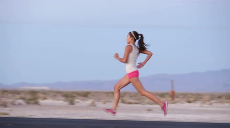 kimerül : Running woman sprinting on highway road at sunset at countryside in USA. Fit female fitness girl training outdoor in beautiful landscape. Multiracial Caucasian Asian female runner in her 20s.