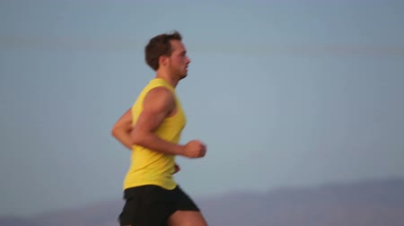kocogó : Running man jogging on road at sunset. Fit male fitness man training outdoor in beautiful at night. Guy runner in his 20s. Stock mozgókép