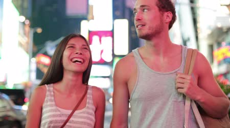 quadrado : Dating young couple happy in love talking and walking on Times Square, New York City at night. Beautiful young multiracial tourists having fun date on Manhattan, USA. Asian woman, Caucasian man.