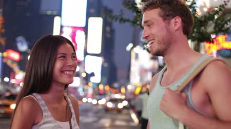 друзья : Dating young couple happy in love talking on Times Square, New York City at night. Beautiful young multiracial tourists having fun date on Manhattan, USA. Asian woman, Caucasian man.