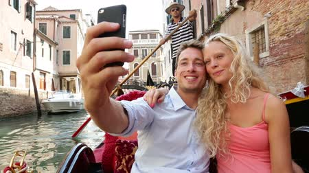 парусный спорт : Couple in Venice on Gondole ride romance in boat happy together on travel vacation holidays. Romantic young beautiful couple taking self-portrait sailing in venetian canal in gondola. Italy. Стоковые видеозаписи