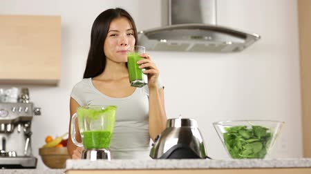 meyve suyu : Green smoothie woman drinking vegetable smoothies giving thumbs up looking at camera. Healthy eating lifestyle young woman having drink with spinach, carrots, celery with blender at home in kitchen. Stok Video