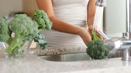 food preparation : Cleaning washing broccoli vegetables in kitchen sink. Close up of woman hands preparing healthy food.