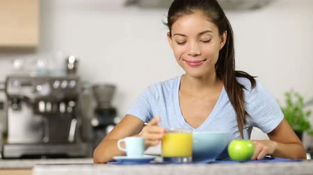 milho : Woman eating breakfast cereals drinking orange juice smiling happy in the morning. Beautiful young multiracial woman sitting in her kitchen at home. Mixed race Asian Caucasian female model.
