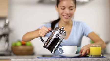 kahvaltı : Coffee - woman making french press coffee at breakfast table in the morning. Girl pouring and drinking coffee at home in kitchen.
