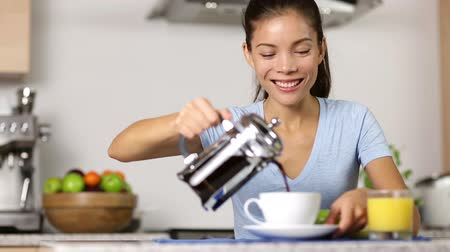 kahvaltı : Woman making french press coffee at breakfast. Happy smiling girl drinking coffee eating breakfast at home in kitchen. Mixed race Asian Caucasian female model.